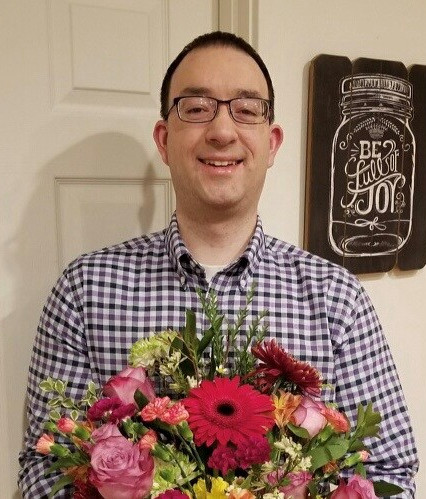 Nick Rusow, Senior Insurance Associate for A.G. Sadowski, holding flowers